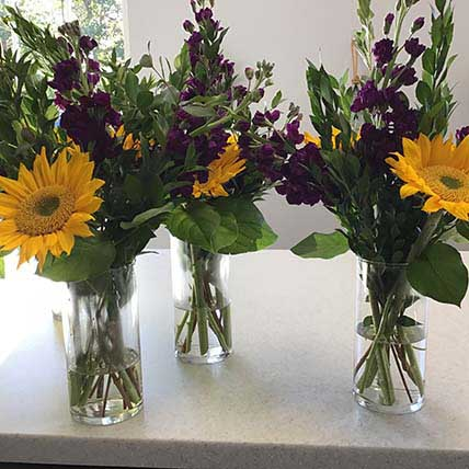 Bright arrangements with sunflowers and purple accents